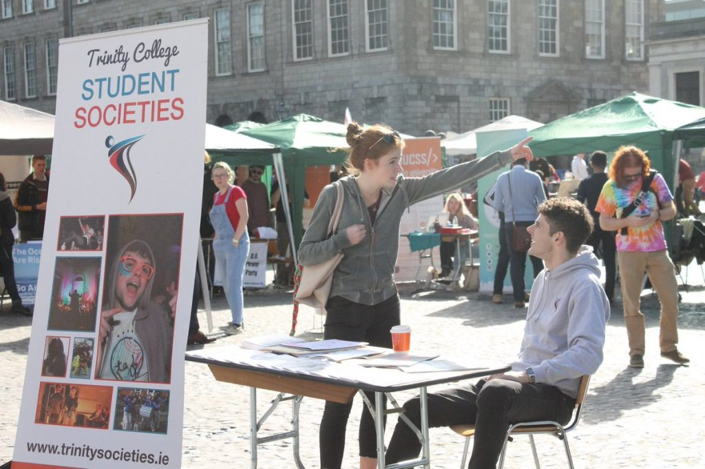 A student asking another student for help at Trinity's Freshers Week Fair.