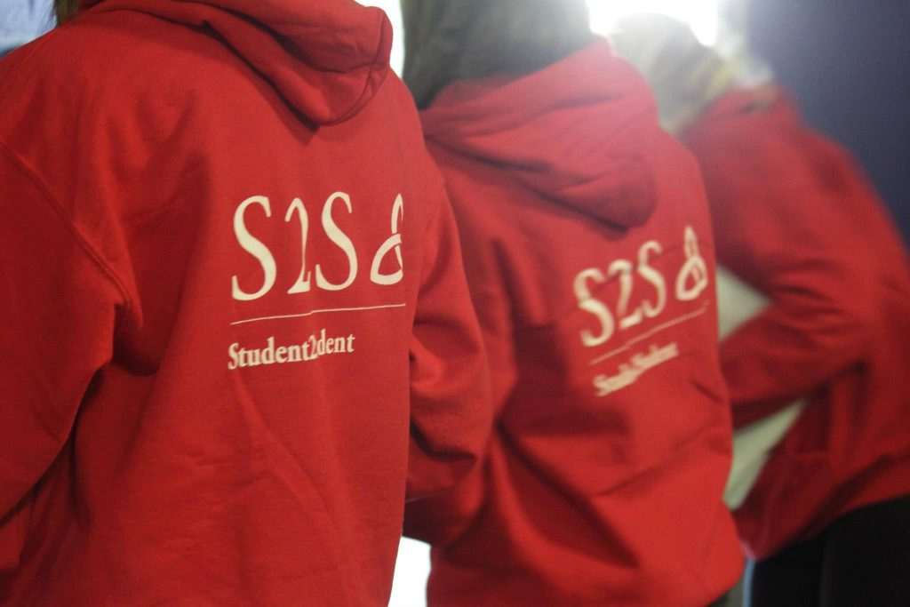 Two students wearing red Student to Student hoodies